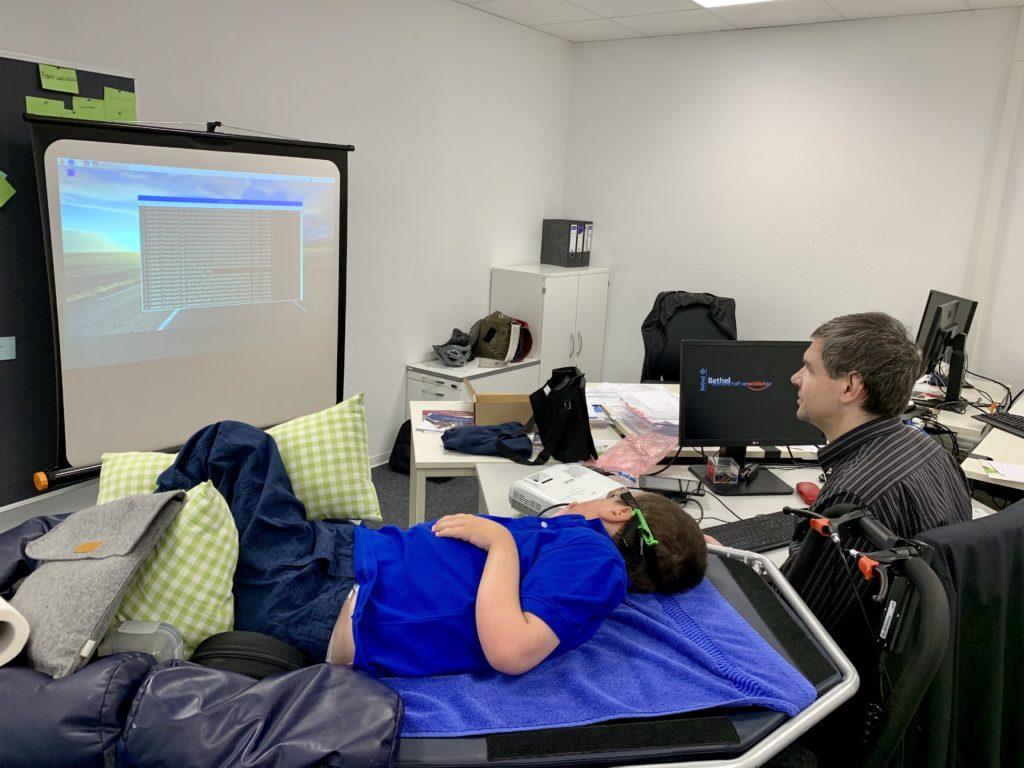 """Auf dem Bild ist Albert zu sehen, wie er mir am Beamer das Betriebssystem """"Linux"""" erklärt."""