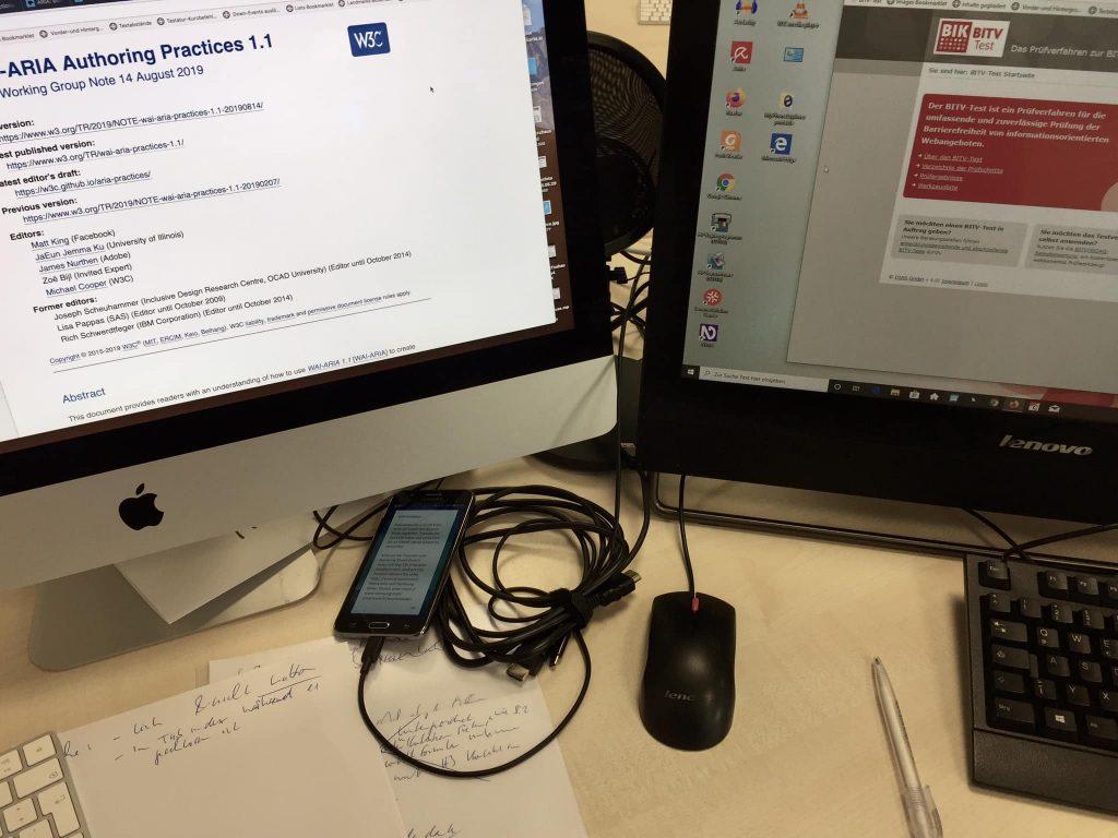 Arbeitsplatz bei PIKSL zum Testen von Internetseiten. Das Bild zeigt zwei Monitore mit Internetseiten, ein Smartphone und handbeschriebene Zettel.